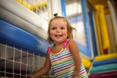 Petit bébé caucasien dans le terrain de jeu La petite fille monte le St Photo libre de droits