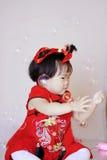 Petit bébé chinois heureux dans les bulles de savon rouges de jeu de cheongsam Photographie stock libre de droits