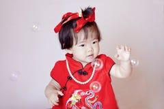 Petit bébé chinois mignon dans les bulles de savon rouges de jeu de cheongsam Photo stock