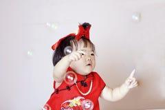 Petit bébé chinois mignon dans les bulles de savon rouges de jeu de cheongsam Photos libres de droits
