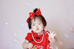Petit bébé chinois mignon dans les bulles de savon rouges de jeu de cheongsam Image libre de droits