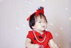 Petit bébé chinois mignon dans les bulles de savon rouges de jeu de cheongsam Photo libre de droits
