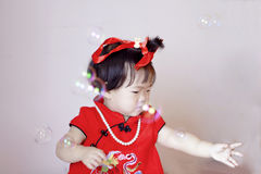 Petit bébé chinois mignon dans les bulles de savon rouges de jeu de cheongsam Photos stock