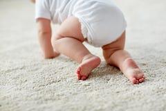 Petit bébé dans la couche-culotte rampant sur le plancher à la maison photos libres de droits