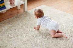 Petit bébé dans la couche-culotte rampant sur le plancher à la maison photo libre de droits