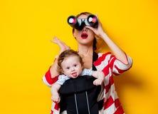 Petit bébé dans le transporteur et la mère avec des jumelles photo libre de droits