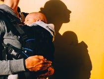 Petit bébé dans le transporteur et la mère avec le prix sur le fond jaune photo stock