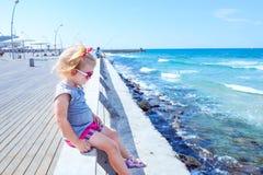 Petit bébé de Blondy 2 ou 3 ans dans des lunettes de soleil roses seul se reposant sur la balustrade en bois de mer sur le bord d images libres de droits