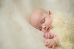 Petit bébé de jambe sur le lit Images stock