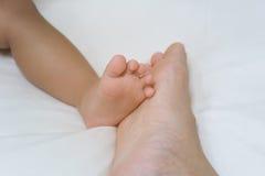 Petit bébé de pied et grand père de pied Photos stock