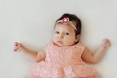 Petit bébé de sourire avec les yeux écarquillés très mignon dans une robe rose se situant dans la couverture blanche photos stock