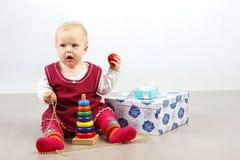 petit bébé fâché seul s'asseyant avec des présents et des jouets photographie stock