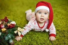 Petit bébé garçon avec du charme dans les chapeaux et des pyjamas rouges de Santa avec le snowf Image libre de droits
