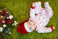 Petit bébé garçon avec du charme dans les chapeaux et des pyjamas rouges de Santa avec le snowf Images libres de droits