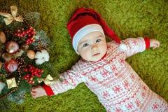 Petit bébé garçon avec du charme dans les chapeaux et des pyjamas rouges de Santa avec le snowf Photos libres de droits