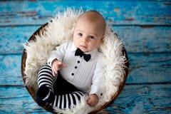 Petit bébé garçon avec le chapeau et le pantalon tricotés de coccinelle dans un panier Photos stock