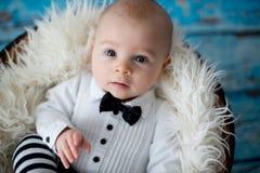Petit bébé garçon avec le chapeau et le pantalon tricotés de coccinelle dans un panier Image libre de droits