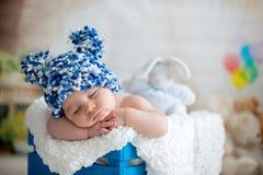 Petit bébé garçon avec le chapeau tricoté, dormant avec l'ours de nounours mignon images libres de droits