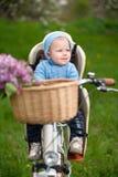 Petit bébé garçon avec un capot se reposant dans la chaise de bicyclette Images stock