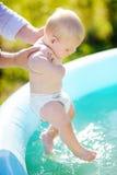 Petit bébé garçon ayant l'amusement par la piscine gonflable Photos libres de droits