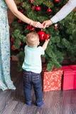 Petit bébé garçon décorant des jouets d'un arbre de Noël Vacances, cadeau, et concept de nouvelle année Photos libres de droits