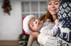 Petit bébé garçon dans le father& x27 ; mains de s, jeune mère regardant le fils Image stock