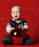 petit bébé garçon heureux avec la boule à la maison au-dessus de la neige images stock