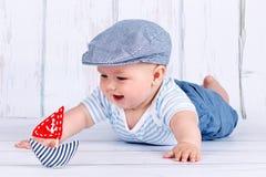 Petit bébé garçon heureux avec un bateau Photos stock