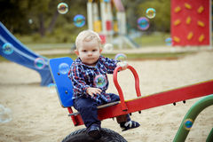 Petit bébé garçon heureux jouant sur le terrain de jeu pendant l'été Photographie stock libre de droits
