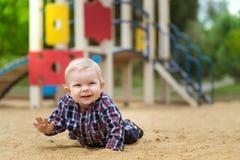 Petit bébé garçon heureux jouant sur le terrain de jeu pendant l'été Photos stock