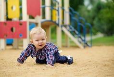 Petit bébé garçon heureux jouant sur le terrain de jeu pendant l'été ou Photos libres de droits