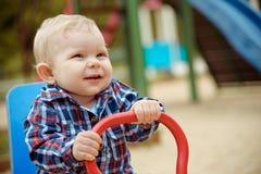 Petit bébé garçon heureux jouant sur le terrain de jeu pendant l'été ou l'automne Photographie stock libre de droits
