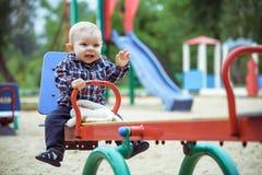 Petit bébé garçon heureux jouant sur le terrain de jeu pendant l'été ou l'automne Photos stock