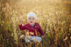 Petit bébé garçon heureux s'asseyant et souriant sur un pré sur la nature dans le jour ensoleillé d'été image libre de droits