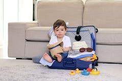 Petit bébé garçon mignon avec l'expression drôle de visage se reposant dans le chapeau de paille bleu de participation de valise  photo libre de droits