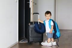 Petit bébé garçon mignon dans des chaussures de pères et avec le grand sac à dos jugeant la valise restant la porte ouverte proch photos stock