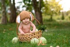 Petit bébé garçon mignon dans le costume du lapin se reposant sur l'herbe dans le panier avec le chou et la carotte Photographie stock