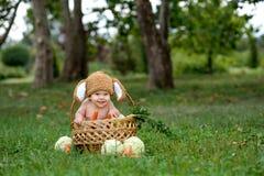 Petit bébé garçon mignon dans le costume du lapin se reposant sur l'herbe dans le panier avec le chou et la carotte Photo stock