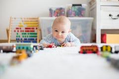 Petit bébé garçon mignon, jouant avec des voitures de jouet sur le tapis dans le chi Image stock