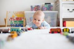 Petit bébé garçon mignon, jouant avec des voitures de jouet sur le tapis dans le chi Photos stock