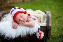 Petit bébé garçon nouveau-né doux, dormant dans la caisse avec la PA tricotée images stock