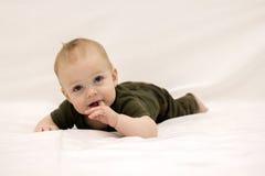 Petit bébé garçon réfléchi sur le lit Photo libre de droits