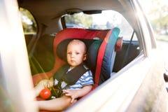 Petit bébé garçon s'asseyant dans le siège de voiture dans la voiture Photographie stock libre de droits