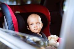 Petit bébé garçon s'asseyant dans le siège de voiture dans la voiture Photo stock