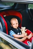 Petit bébé garçon s'asseyant dans le siège de voiture dans la voiture Photos libres de droits