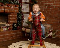 Petit bébé garçon sur le cheval de basculage, habillé dans le chandail et des jeans Décorations de Noël ou de nouvelle année Photo stock