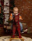 Petit bébé garçon sur le cheval de basculage, habillé dans le chandail et des jeans Décorations de Noël ou de nouvelle année Photos stock