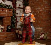 Petit bébé garçon sur le cheval de basculage, habillé dans le chandail et des jeans Décorations de Noël ou de nouvelle année photographie stock