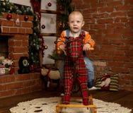 Petit bébé garçon sur le cheval de basculage, habillé dans le chandail et des jeans Décorations de Noël ou de nouvelle année image stock