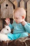 Petit bébé heureux avec un petit lapin blanc Photos stock